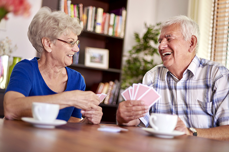 Elderly couple playing cards in an assisted living facility