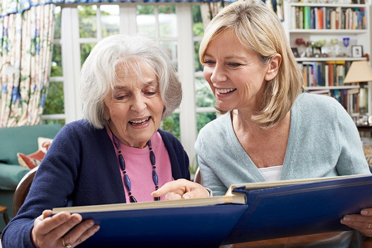 Elderly woman and caregiver looking through a photo album in a memory care facility