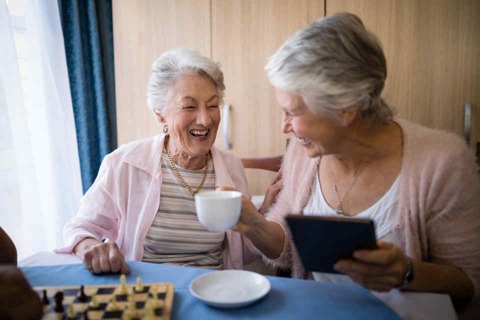 Two elderly women having coffee in an assisted living facility