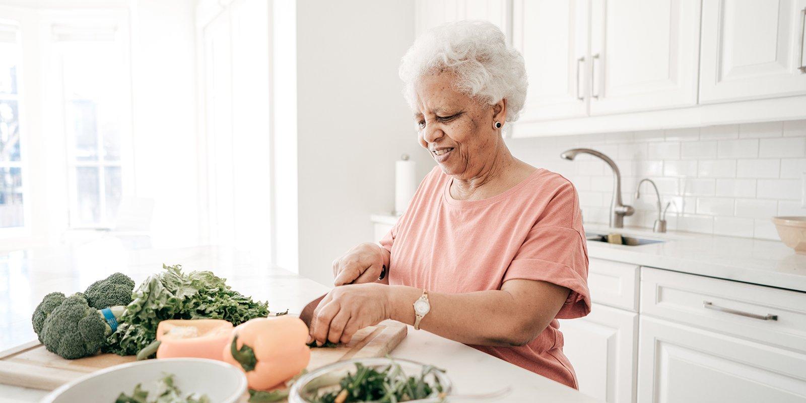 elderly woman chopping vegetables in kitchen